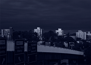 monochrome landscape featuring four apartment blocks on the horizon over an expressway early evening